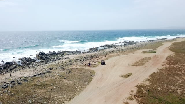 aerial forward: rocky terrain in the beach of oranjestad aruba in oranjestad, aruba - quadbike stock videos & royalty-free footage