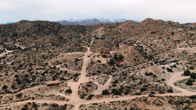aerial forward: scattered houses along dirt road in mojave desert with scrappy shrub and distant mountains - yucca stock videos & royalty-free footage