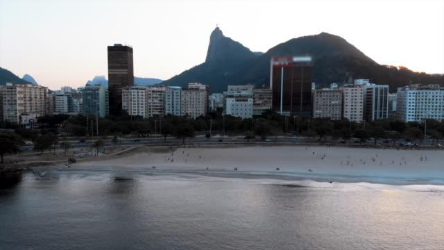 aerial forward: scenic beach and modern buildings in rio de janeiro at dusk - リオデジャネイロ点の映像素材/bロール
