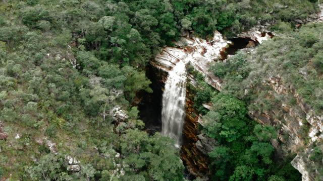 vídeos de stock, filmes e b-roll de aerial forward: scenic waterfall in the lush green jungle in chapada, brazil - riacho