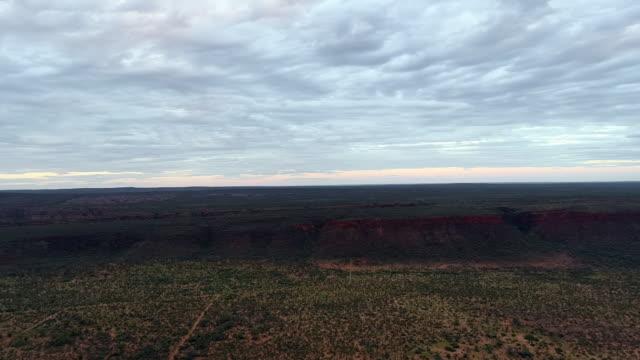 aerial forward: shadow and plant covered flat plain with cloudy sky above - uluru, australia - naturligt landmärke bildbanksvideor och videomaterial från bakom kulisserna
