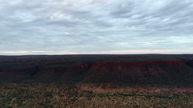 aerial forward: shadow, plant covered flat plain with cloudy sky above - uluru, australia - エアーズロック点の映像素材/bロール
