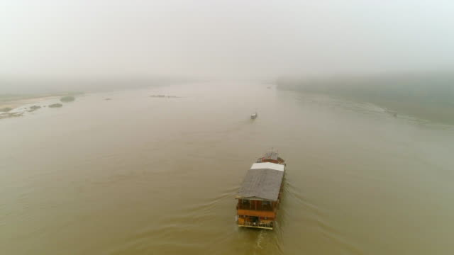 vídeos de stock e filmes b-roll de aerial forward shot of cruise ship moving in river during foggy weather, drone flying over water - mekong river, laos - cruzeiro