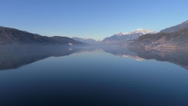 aerial forward shot of lake millstatt amidst mountains against clear blue sky - radenthein, austria - völlig lichtdurchlässig stock-videos und b-roll-filmmaterial