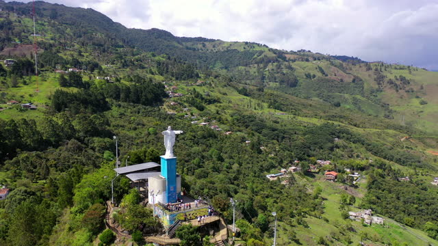aerial forward shot of monument on mountain against sky, drone flying over natural landscape - medellin, colombia - religion stock-videos und b-roll-filmmaterial