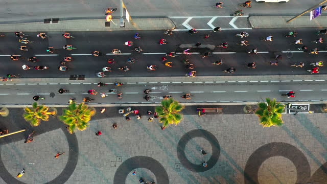 aerial forward shot of people cycling on road during rally in city, drone flying over tress on sidewalk - tel aviv, israel - land vehicle stock videos & royalty-free footage