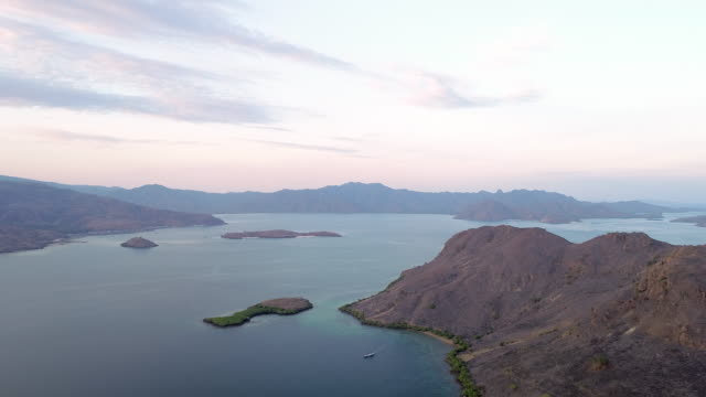 aerial forward slow: horizon and the mountains of komodo island of indonesia - insel komodo stock-videos und b-roll-filmmaterial