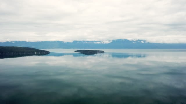 Aerial Forward Slow: Island Lake of Flathead Surrounded by Water Reflections