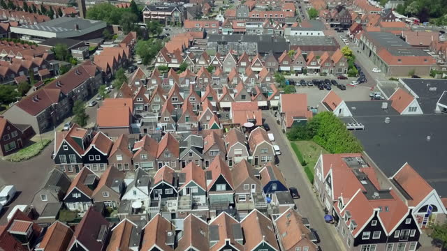 aerial forward slow: pointed roof of homes under the hot sun - volendam, netherlands - aerial stock videos & royalty-free footage