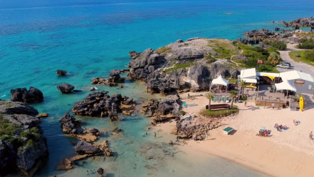 aerial forward slow: remote beach architecture with surrounding rock formations in spanish point, bermuda - weathered stock videos and b-roll footage