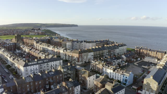 aerial forward slow: town near the vast waters of the area - whitby, england - town stock videos & royalty-free footage
