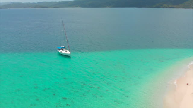aerial forward: small yacht near the shores of cocuyo beach with view of island - hispaniola stock videos & royalty-free footage
