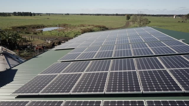 aerial forward: solar panels on farm building on grassy plain, queensland, australia - farm stock videos & royalty-free footage