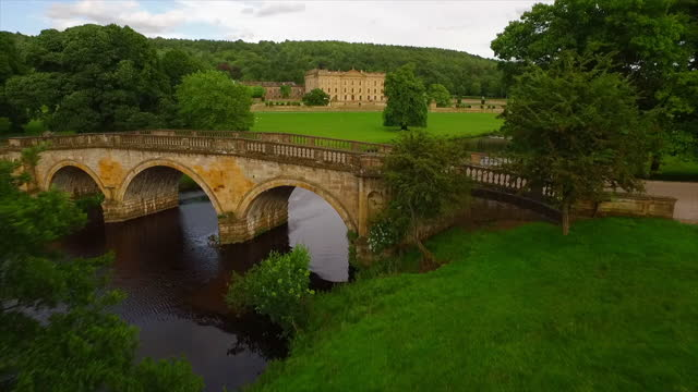 aerial forward: stone bridge and wide green field leading up to stately georgian great home surrounded by forest - chatsworth, united kingdom - royalty stock videos & royalty-free footage