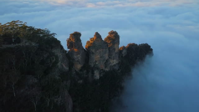aerial forward: stunning famous three sisters rock formation in thick clouds, blue mountains, australia - three people stock videos & royalty-free footage