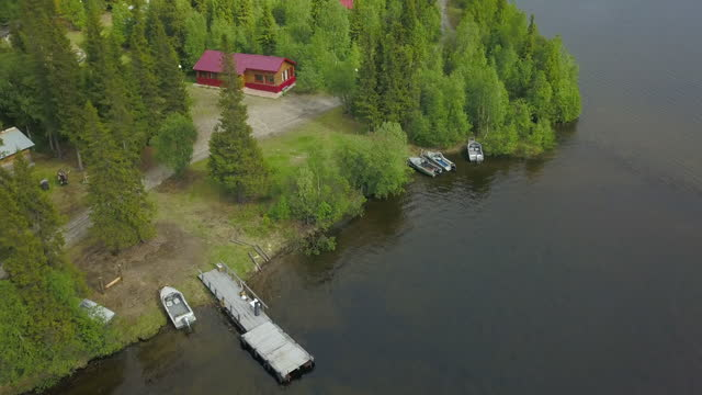 aerial forward tilt: cottages by green trees near lake - lapland nature reserve, russia - lake stock videos & royalty-free footage
