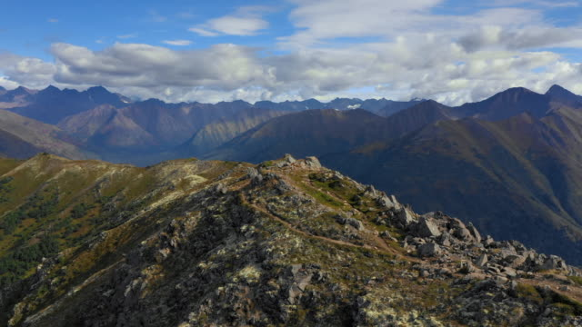 aerial forward: top of rocky, grassy mountain with mountains out to horizon and blue sky above - chugach national forest, alaska - chugach national forest stock videos & royalty-free footage