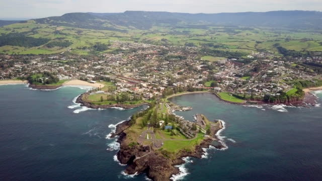 aerial forward: town in green valley by ocean on sunny day, wollongong, australia - town stock videos & royalty-free footage
