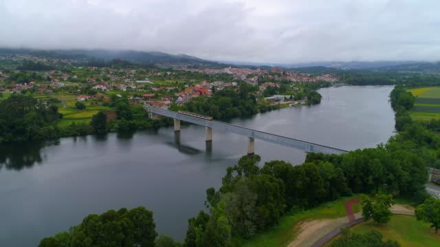 Aerial Forward: Train Passing Short Bridge Over the Water in Valenca Portugal