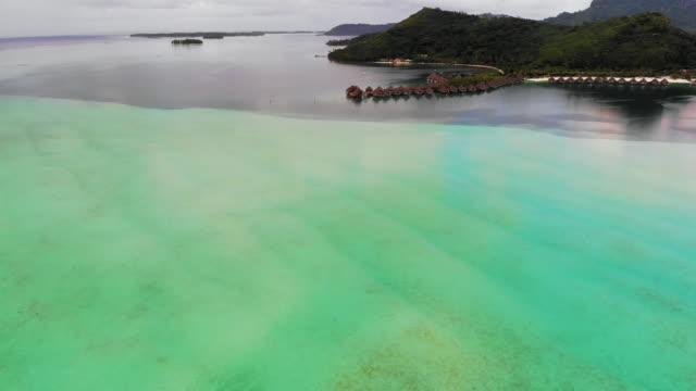 aerial forward: tropical huts in marble green and blue ocean in bora bora, french polynesia - bora bora aerial stock videos and b-roll footage