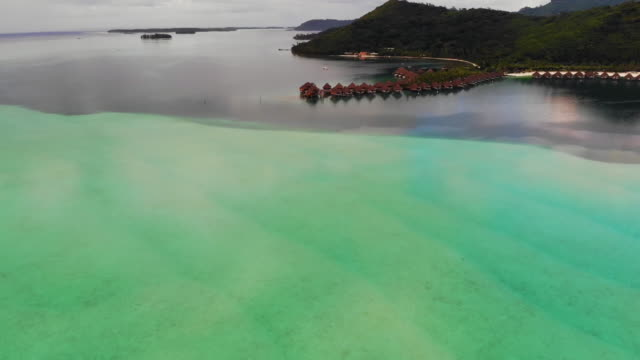 aerial forward: vacation homes in marble green ocean by mountains in bora bora, french polynesia - insel tahiti stock-videos und b-roll-filmmaterial