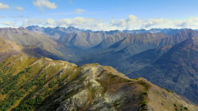 aerial forward: vast mountains out to horizon, with sunny tops and shadow filled valleys - chugach national forest, alaska - chugach national forest stock videos & royalty-free footage
