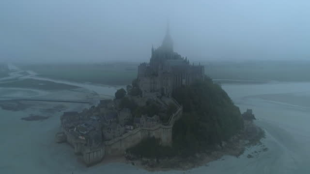 vidéos et rushes de aerial forward: village and abbey of mont saint-michel in fog on gloomy day - normandy, france - moyen âge