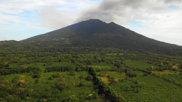 aerial forward: volcano in green valley with smoke above - ometepe, nicaragua - nicaragua stock videos & royalty-free footage