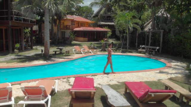 vidéos et rushes de aerial forward: woman walking around the pool in cabarete beach - de petite taille