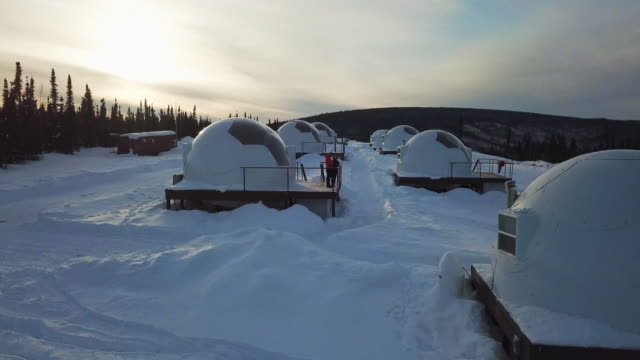 aerial forward/ascend: igloo homes on snowy plain by forest valley, fairbanks, alaska - valley stock videos & royalty-free footage