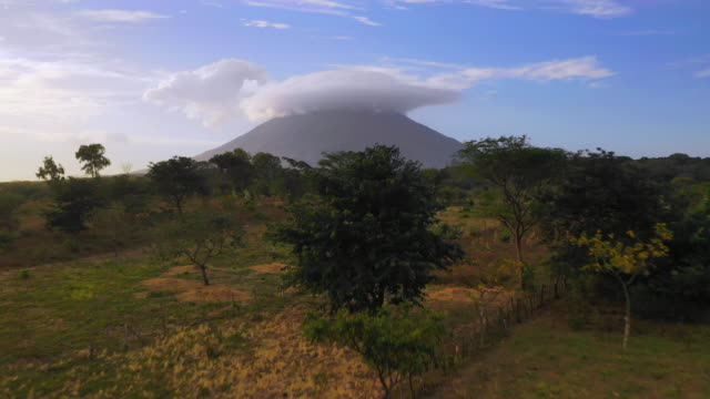 aerial forward/ascend: volcano in green valley with smoke above  - ometepe, nicaragua - nicaragua stock videos & royalty-free footage
