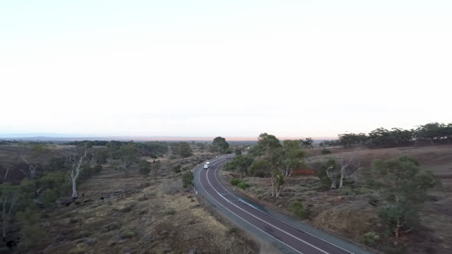 aerial forward/descend: cars on road surrounded by flat plain - uluru, australia - hill stock videos & royalty-free footage