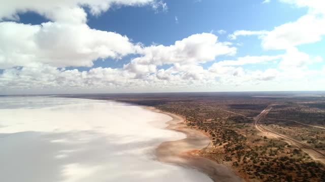 aerial forward/pan down: flat plain with bushes next to white sand with shadows - uluru, australia - northern territory australia stock videos & royalty-free footage