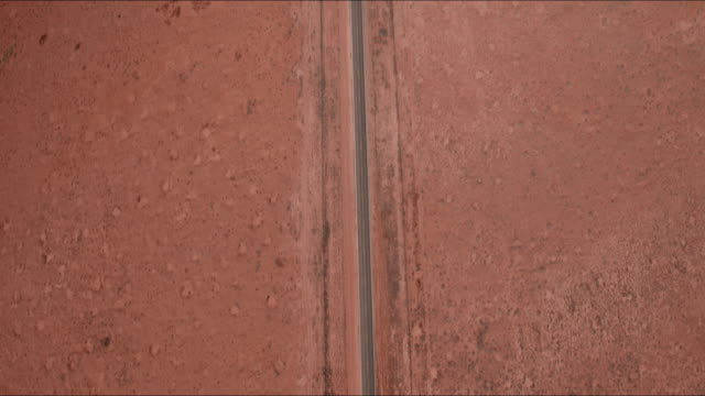 aerial forward/pan up: car driving down road in desert plain toward horizon in monument valley, ut - richtung stock-videos und b-roll-filmmaterial
