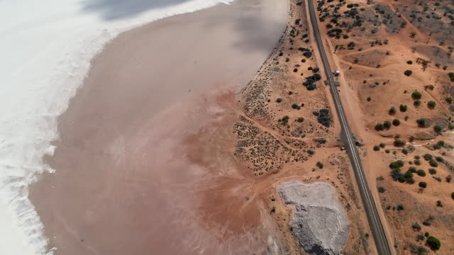aerial forward/pan up: flat plain next to white sand, moving clouds - uluru, australia - エアーズロック点の映像素材/bロール