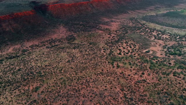 aerial forward/pan up: red mountains on large plain with cloudy sky above - uluru, australia - arid stock videos & royalty-free footage