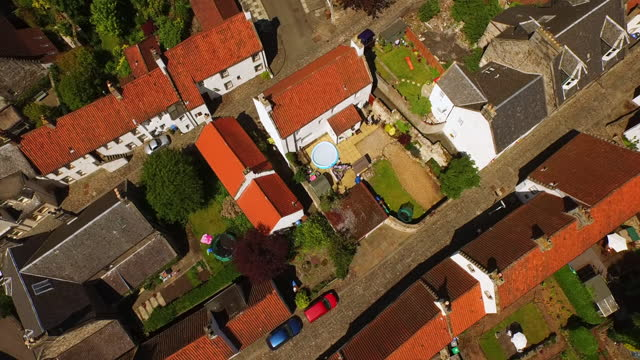 aerial from above small cars driving around tile roofed cottages in village with green gardens and trees - culross, scotland - railway track stock videos & royalty-free footage