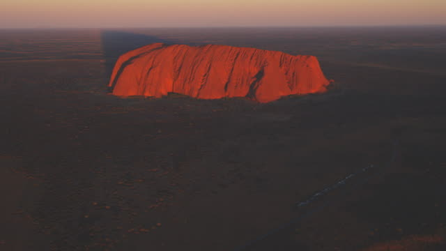 aerial ws tu from open bush and road to reveal uluru at sunrise - エアーズロック点の映像素材/bロール