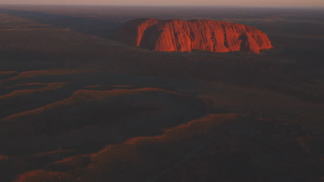 Aerial WS PAN from open bush to reveal Uluru at sunrise