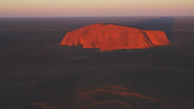 aerial ws tu from open bush to reveal uluru at sunrise - エアーズロック点の映像素材/bロール