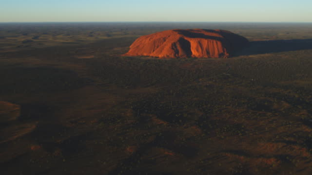 aerial ws tu from open bush to reveal uluru in early morning sun - エアーズロック点の映像素材/bロール