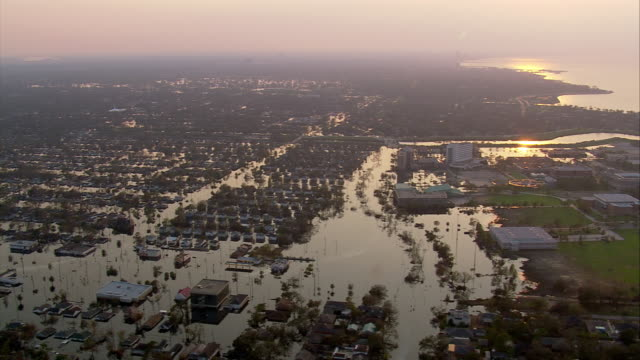 vídeos de stock, filmes e b-roll de aerial from southern shore of lake ponchartrain over houses submerged in water / sunset / louisiana - 2005