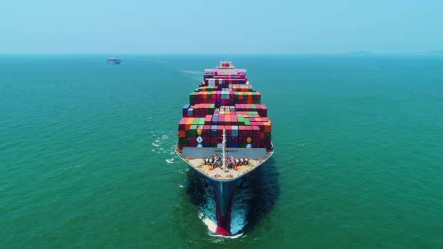 aerial front view container cargo ship full speed with beautiful wave pattern carrier container from terminal commercial port or container warehouse transport on the sea. for business logistics, import export, shipping or freight transportation. - container stock videos & royalty-free footage