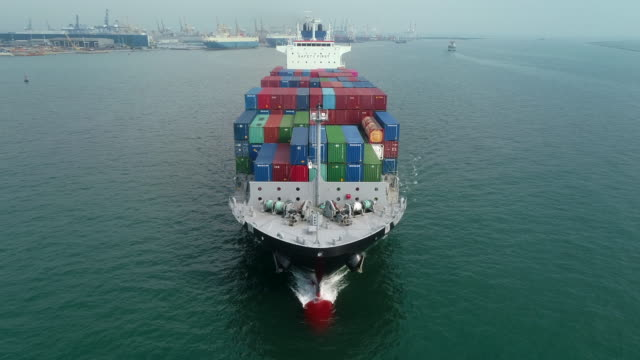 vídeos de stock e filmes b-roll de aerial front view container cargo ship with commercial loading dock background for logistics business , shipping , import export or transportation. - navio cargueiro