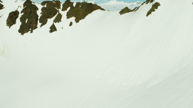vídeos de stock e filmes b-roll de aerial frozen rock and snow covered mountains alaska - eco tourism