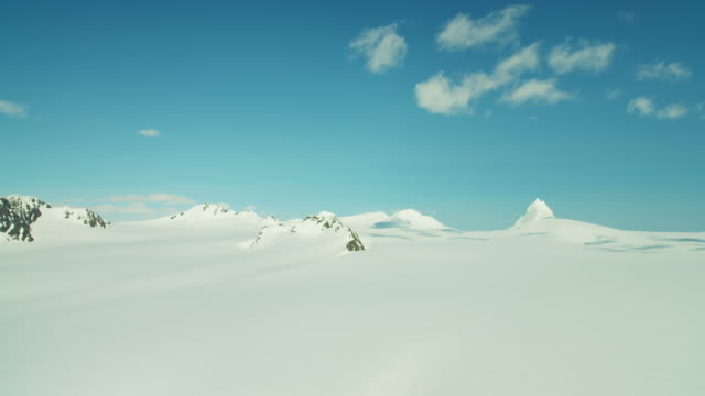 aerial frozen rock and snow covered mountains alaska - frozen stock videos and b-roll footage