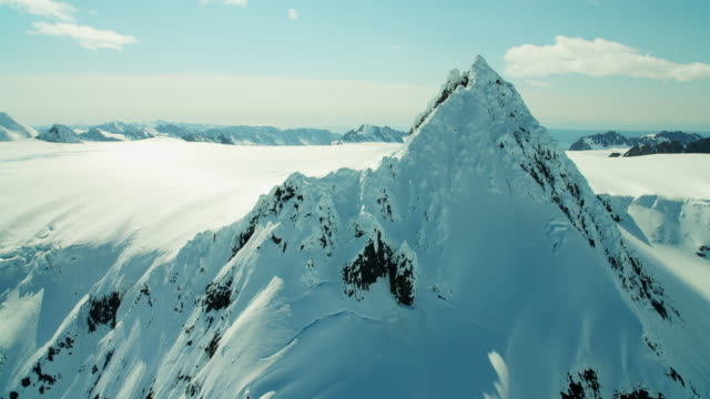 vídeos de stock, filmes e b-roll de aerial frozen rock and snow covered mountains alaska - eco tourism