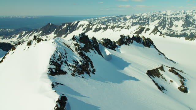 aerial frozen rock and snow covered mountains alaska - eco tourism video stock e b–roll
