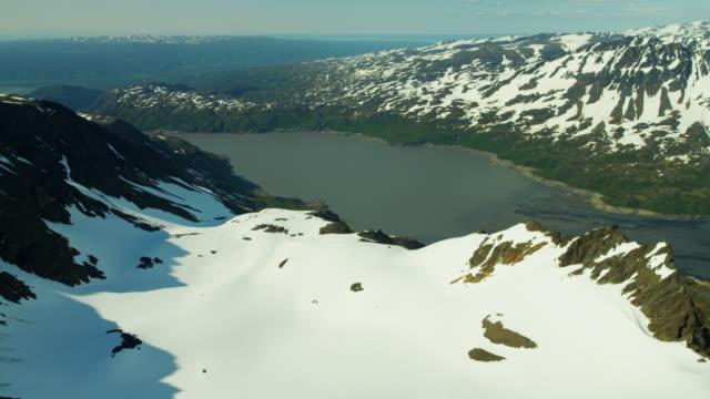 vídeos y material grabado en eventos de stock de aerial frozen rock and snow covered mountains alaska - eco tourism