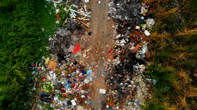 aerial: garbage dump on the outskirts of the forest - pollution stock videos & royalty-free footage